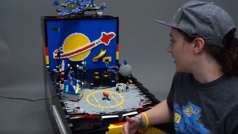 A woman next to a pinball machine made entirely from LEGO bricks.