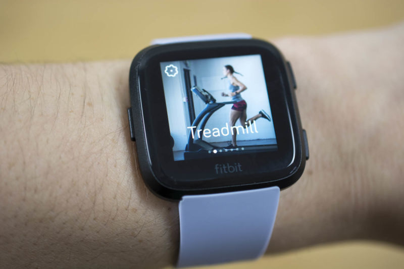 Fitbit Versa smartwatch on a person's wrist with the treadmill activity option on the screen.
