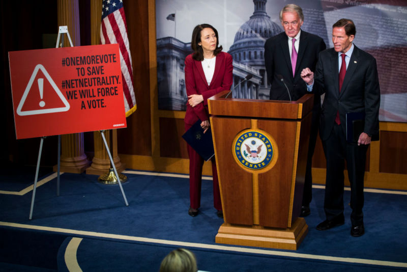 Three Democratic senators speaking next to a sign that says,