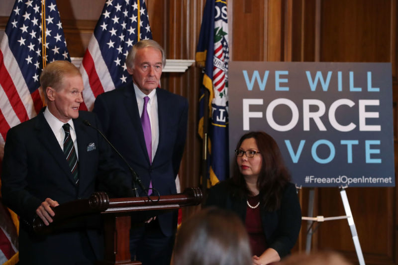 Democratic senators Bill Nelson, Ed Markey, and Tammy Duckworth in front of a sign that says,