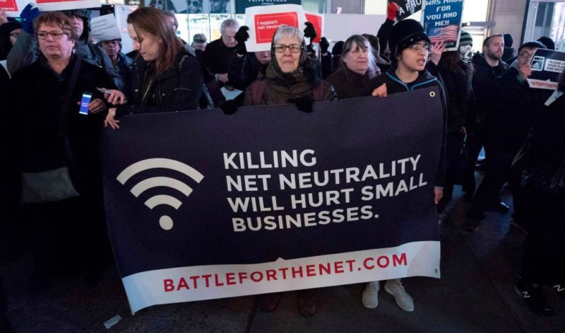 Net neutrality supporters holding a sign that says,