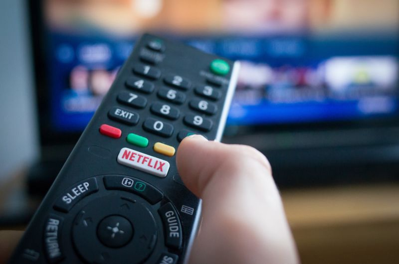 A person's hand holding a TV remote control with a button for Netflix.