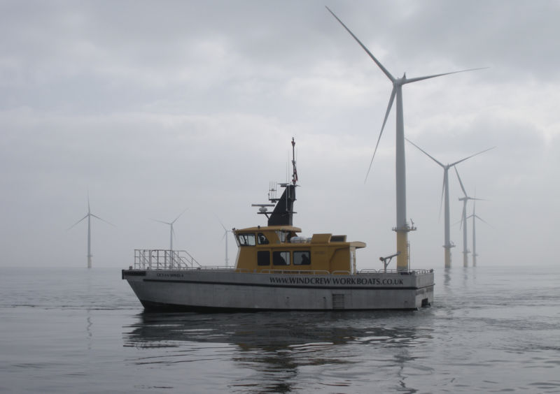 Image of a boat amidst an offshore wind farm.