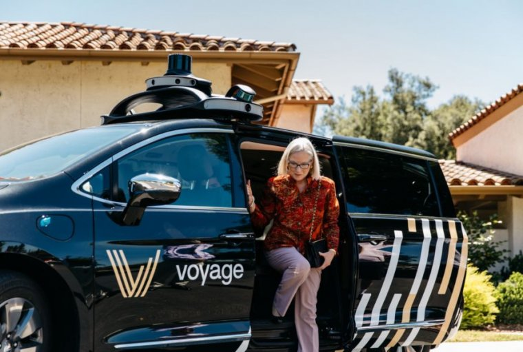 A silver-haired woman steps from a self-driving minivan.