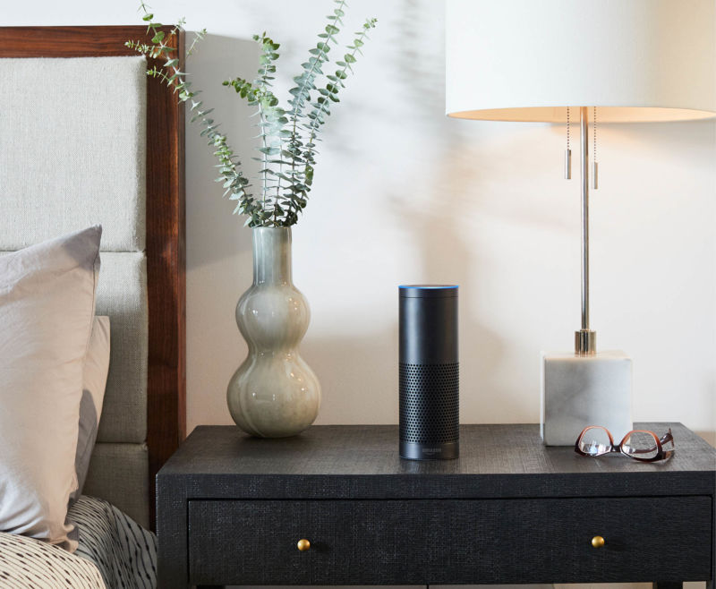 An Amazon Echo speaker sitting on a black nightstand next to a bed in a hotel room.