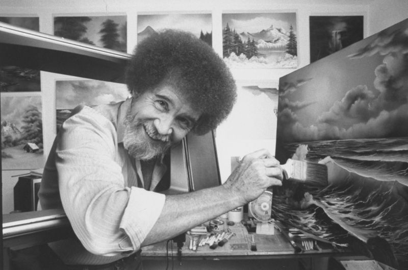 A black and white image of TV painting instructor/artist Bob Ross using a large paint brush to touch up one of his large seascapes in his studio at home.