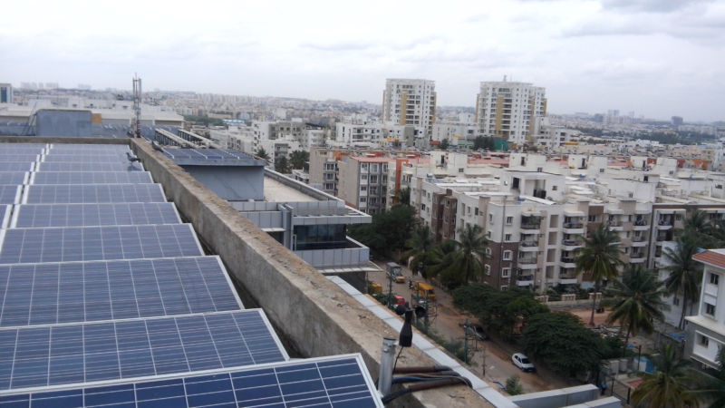Rooftop solar panels overlooking an urban area.
