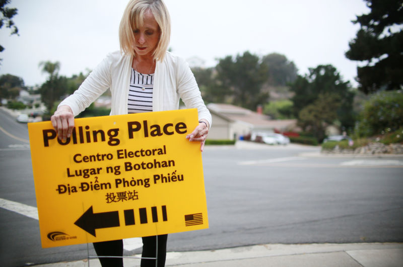 Volunteer Janice MacGurn sets up a polling station sign before opening on primary election day June 5, 2018 in San Diego, California. There are several highly competitive races throughout the state including those for governor and U.S. House and Senate seats.