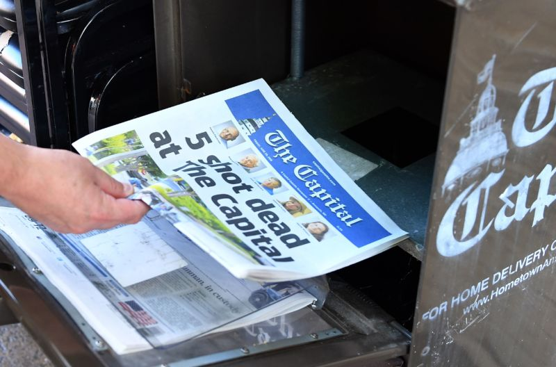Stack of newspapers with headline 5 shot dead at the Capital