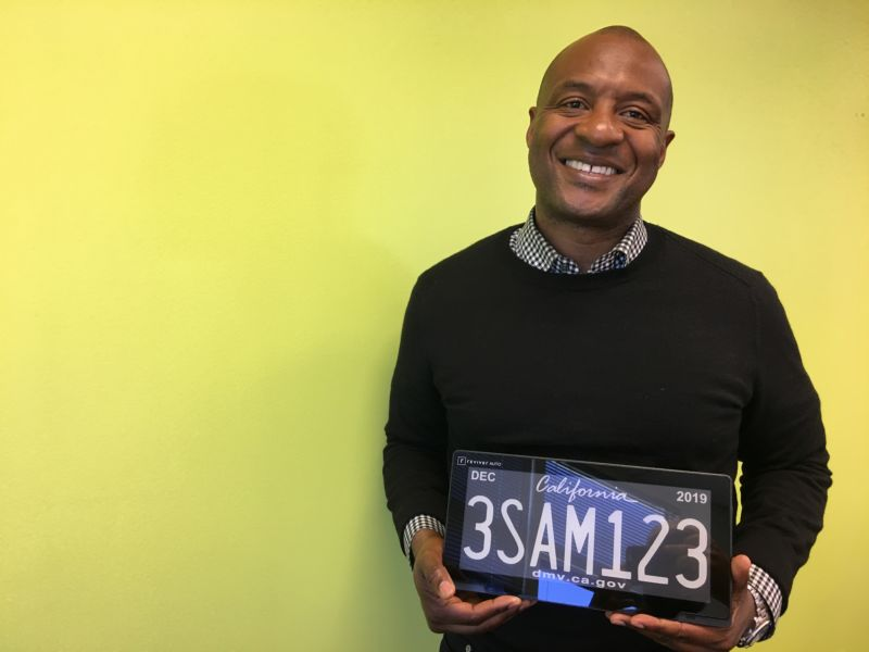 A smiling man holds a digital license plate