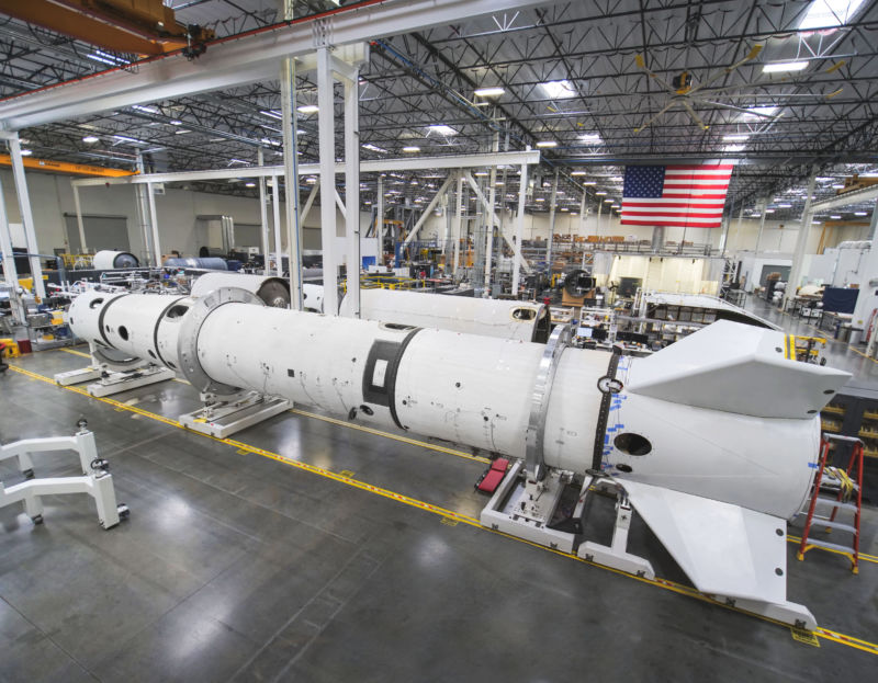 A late May view of the Virgin Orbit factory floor showing an essentially complete LauncherOne in the middle ground, lacking only the payload fairing. This booster will be used for captive carry and drop testing.