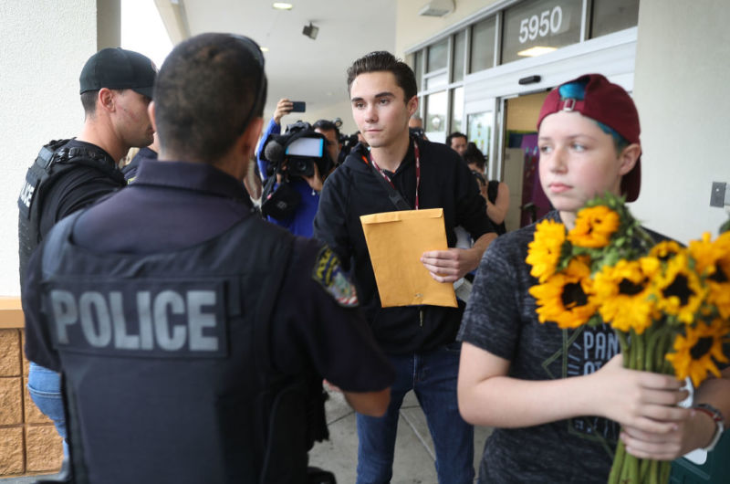 Gun control activist David Hogg shakes hands with a police officer before participating in a protest.