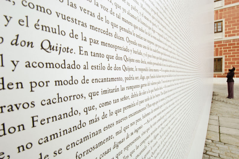 Outdoor wall in Madrid covered in Spanish words possibly from Don Quixote.