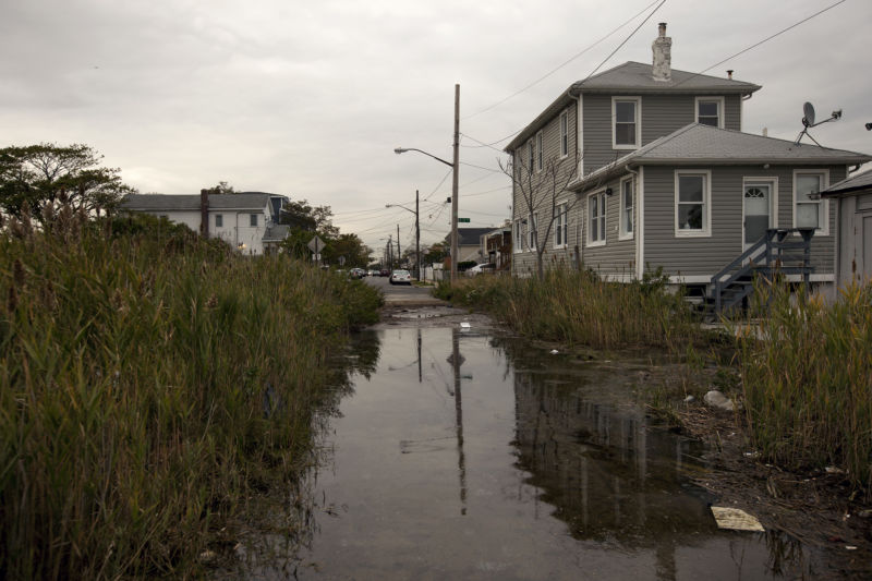 A home at the corner of B 72nd Street and Bayfield Avenue is surrounded by marsh in Averne on the Rockaway peninsula in the Queens borough of New York, US, on Friday, October 10, 2014. Photographer: Michael Nagle/Bloomberg via Getty Images