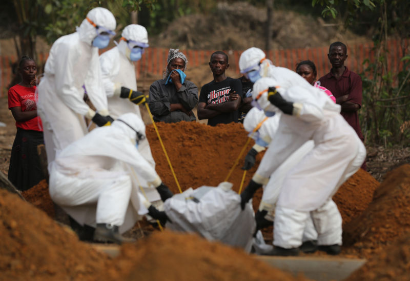 "A family watches as a burial team lowers their loved one into a grave at the US-built cemetery for ""safe burials"" on January 27, 2015 in Disco Hill, Liberia, amid an Ebola epidemic."