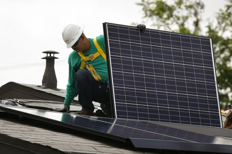 A SolarCity Corp. employee installs a solar panel on the roof of a home in the Eagle Rock neighborhood of Los Angeles, California, on Wednesday, May 7, 2014.