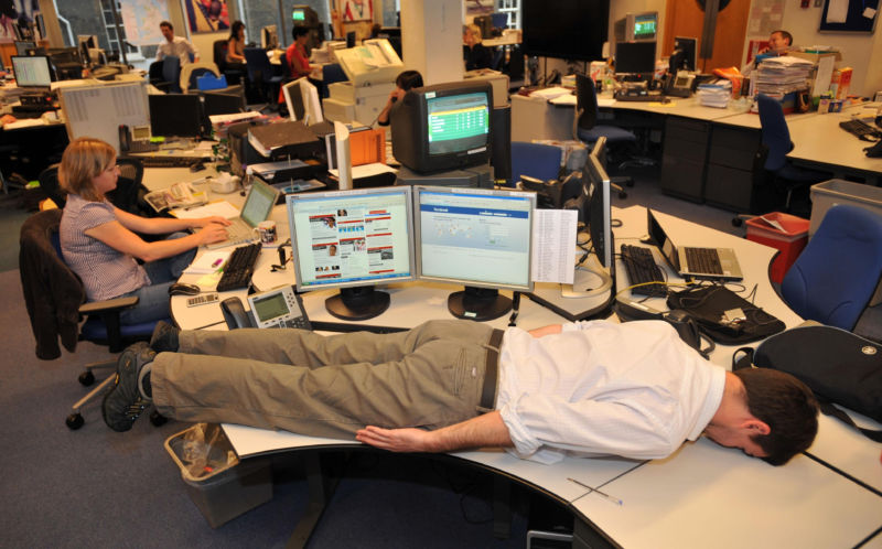 A man lies face down on a desk in an open office