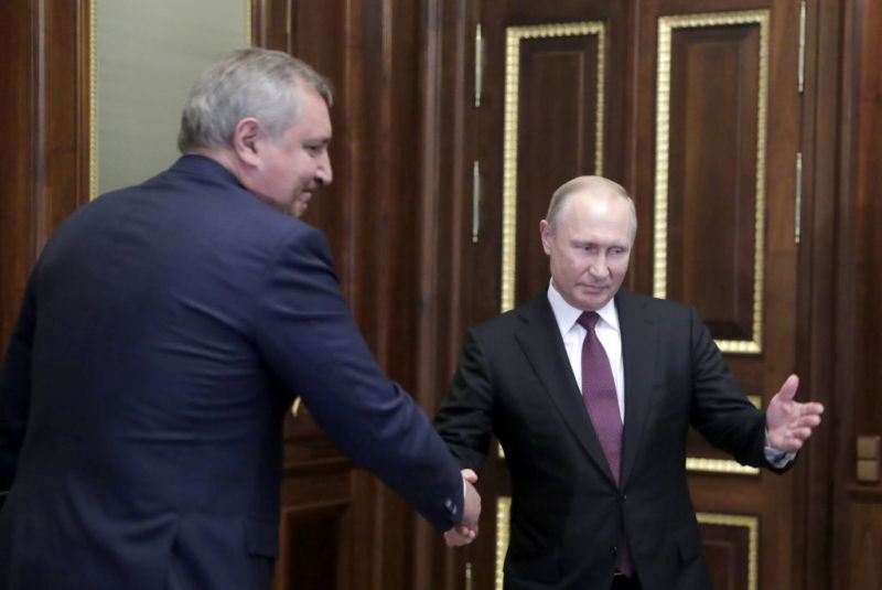 Russia's President Vladimir Putin and former Deputy Prime Minister Dmitry Rogozin shake hands during a meeting at the Konstantin Palace.