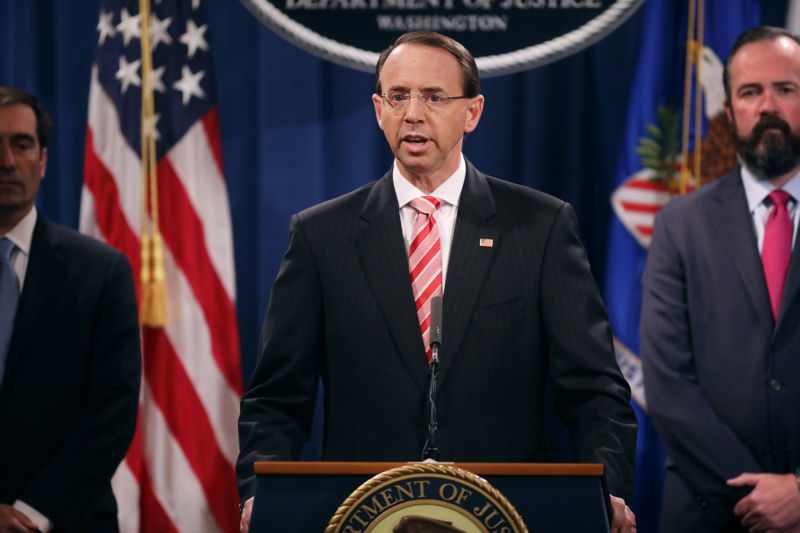 US Deputy Attorney General Rod Rosenstein (C) holds a news conference at the Department of Justice July 13, 2018 in Washington, DC. Rosenstein announced indictments against 12 Russian intelligence agents for hacking computers used by the Democratic National Committee, the Hillary Clinton campaign, the Democratic Congressional Campaign Committee and other organizations.