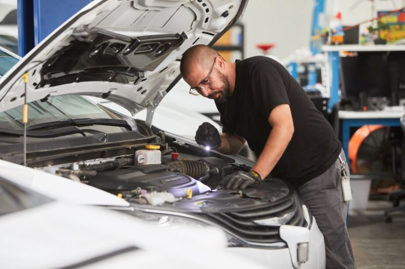 A man in safety goggles looks under the hood of a car.