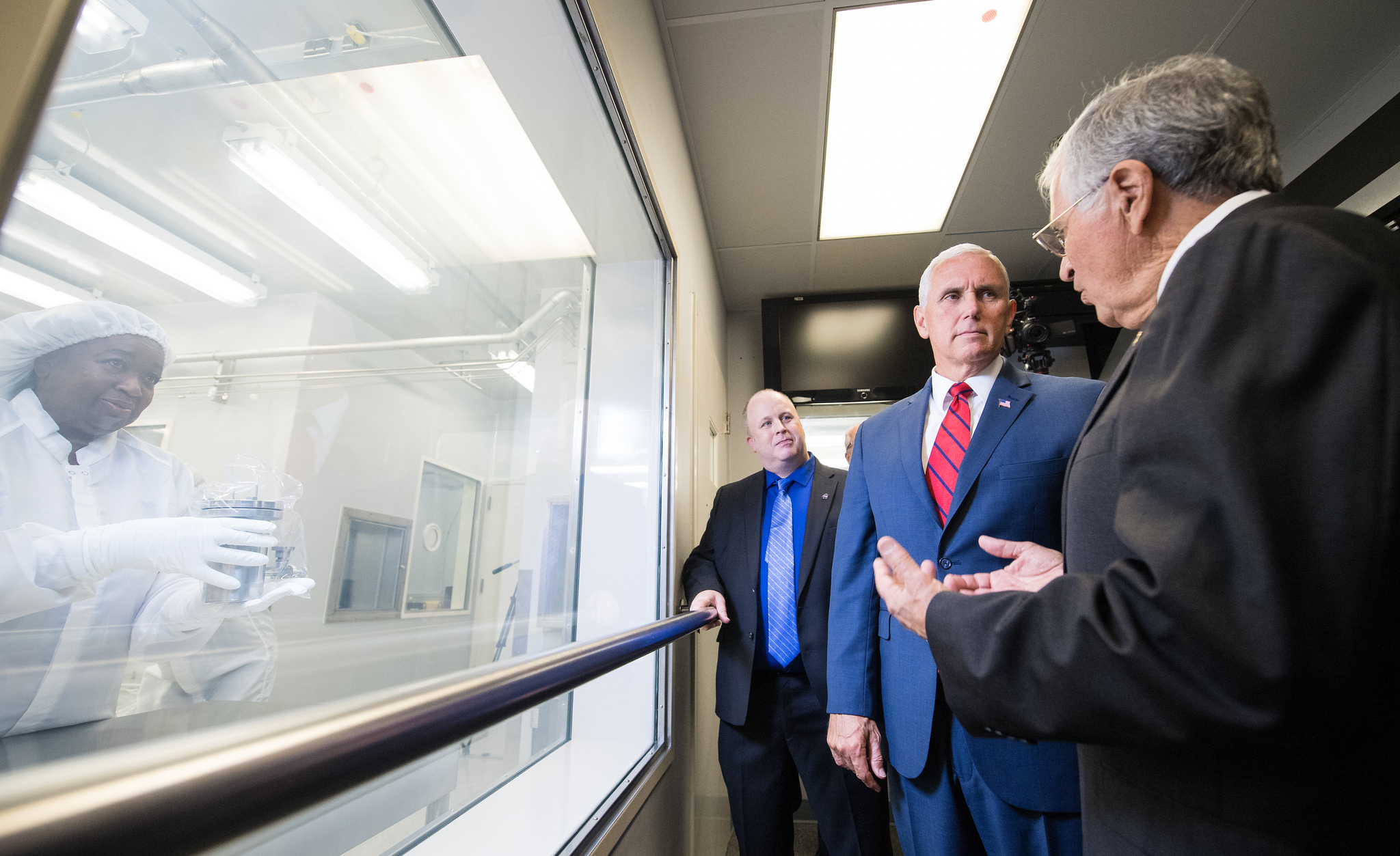 Pence views Sample 15014, which was collected during Apollo 15, with NASA's Apollo Sample Curator Ryan Zeigler, left, and Apollo 17 astronaut Harrison Schmitt, right, in Lunar Curation Laboratory at NASA's Johnson Space Center, Thursday.