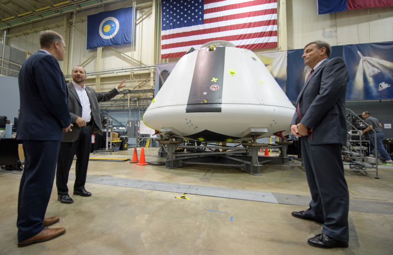 NASA Administrator Jim Bridenstine, left, was shown the Orion test crew capsule that will be used for the Ascent Abort-2 test. NASA's Jon Olansen, second from left, speaks as Orion Program Manager Mark Kirasich looks on.