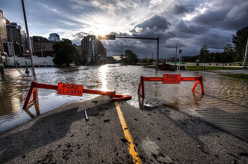 A flooded street with warning barriers.