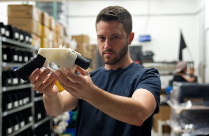 "Cody Wilson, owner of Defense Distributed company, holds a 3D-printed gun, called the ""Liberator,"" in his factory in Austin, Texas, on August 1, 2018."
