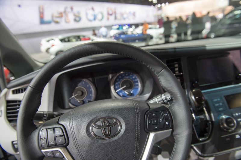 Close-up of steering wheel with autoshow barely visible through windshield.
