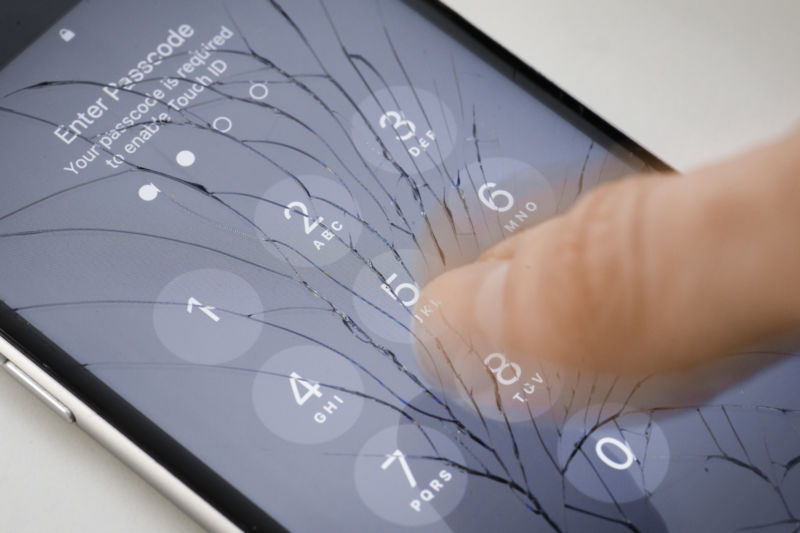 Extreme close-up of a finger unlocking a smartphone.