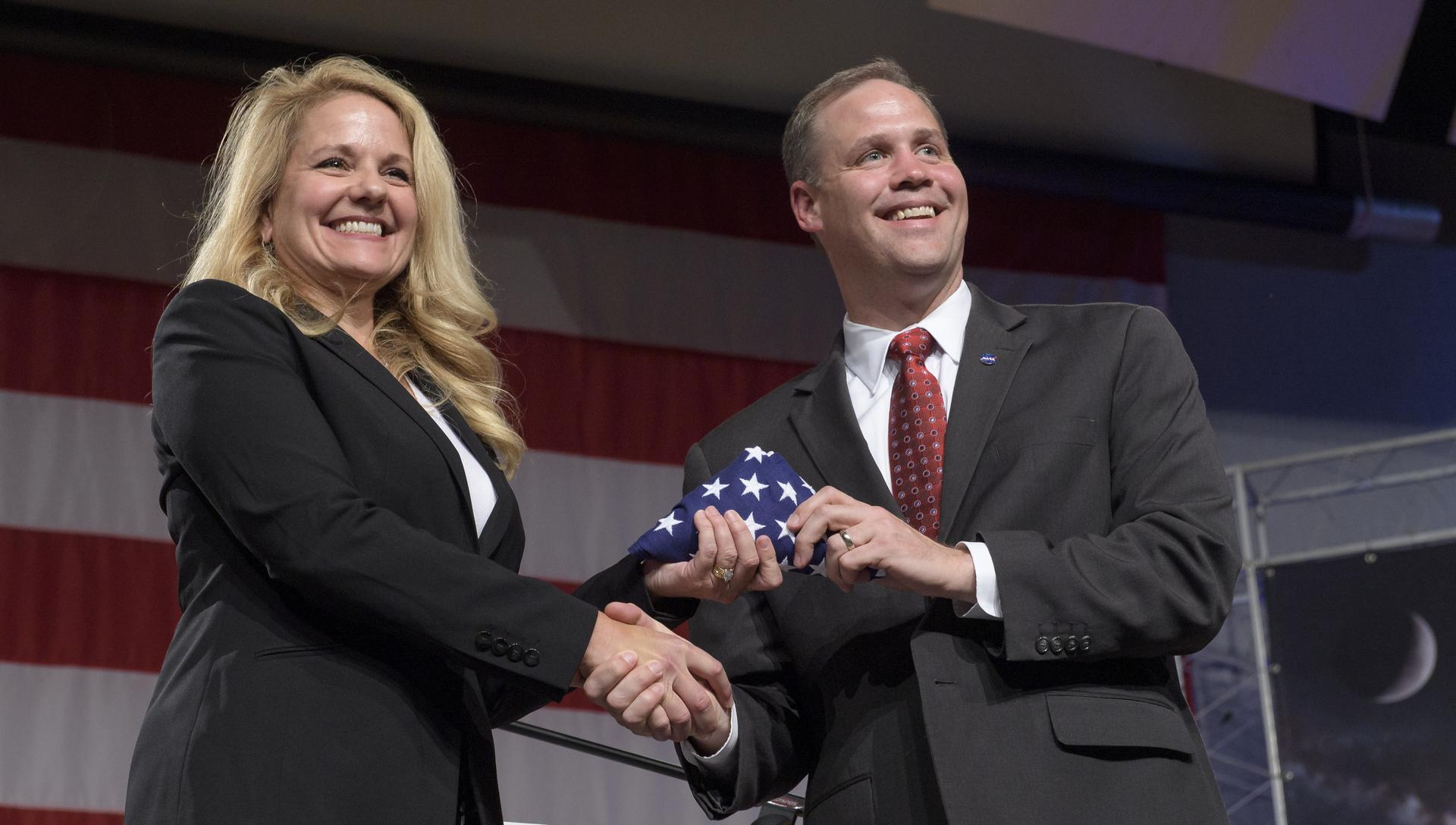 SpaceX President and COO Gwynne Shotwell receives an American flag from NASA Administrator Jim Bridenstine during a NASA event in Houston to announce astronaut crews.