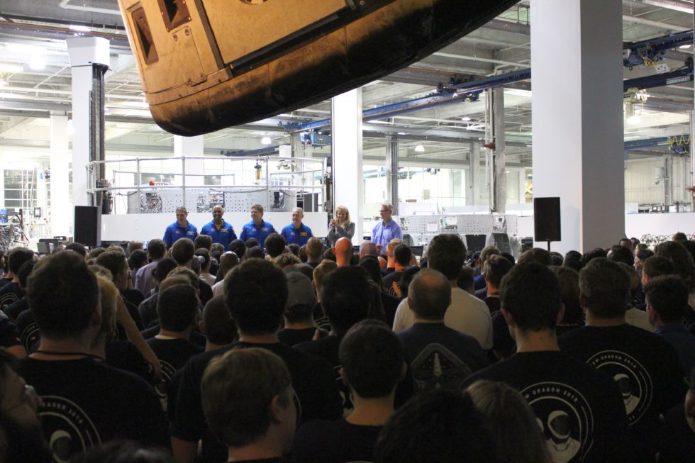 Four astronauts, Gwynne Shotwell, and Benjamin Reed on stage inside the SpaceX factory Monday.