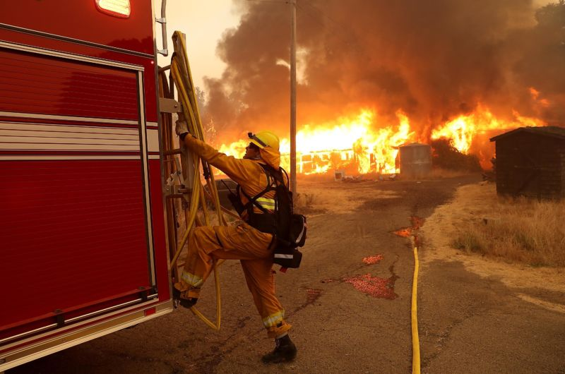 A firefighter pulls a hose away from a horse barn as a fire rages in the background.
