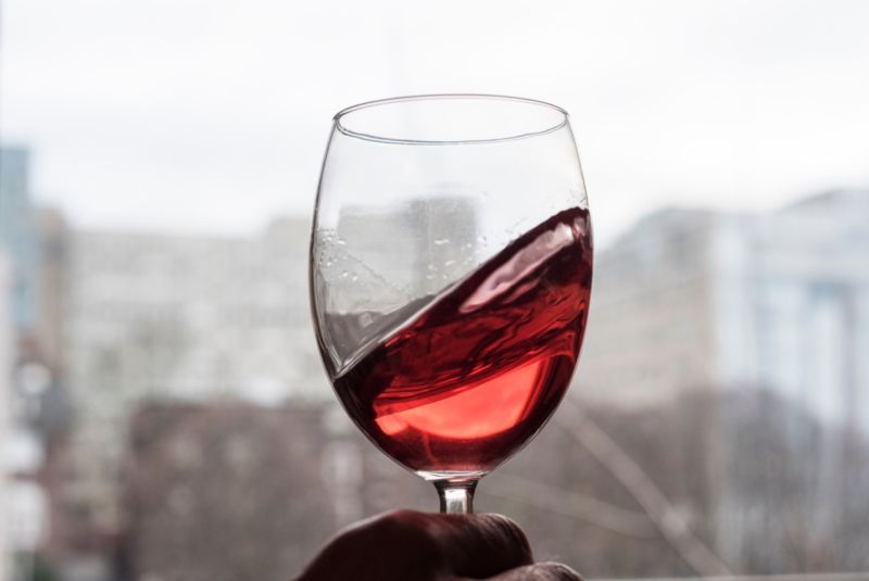 A glass of red wine is held up to a light source while being swirled.