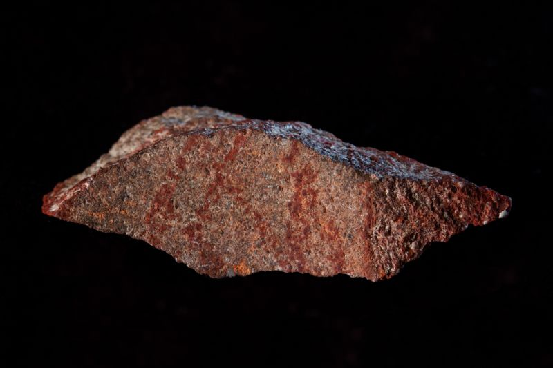 Photo of silcrete flake with ochre crayon cross-hatching on one face