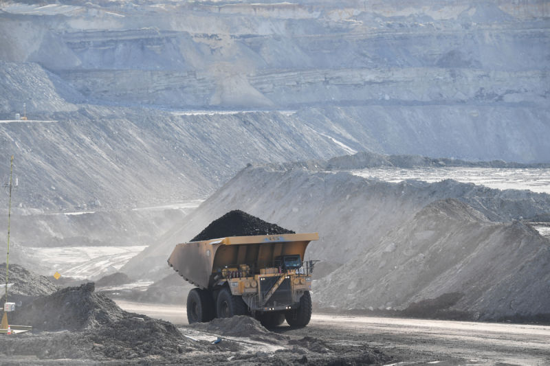 Dumptruck full of coal drives through strip mining area.
