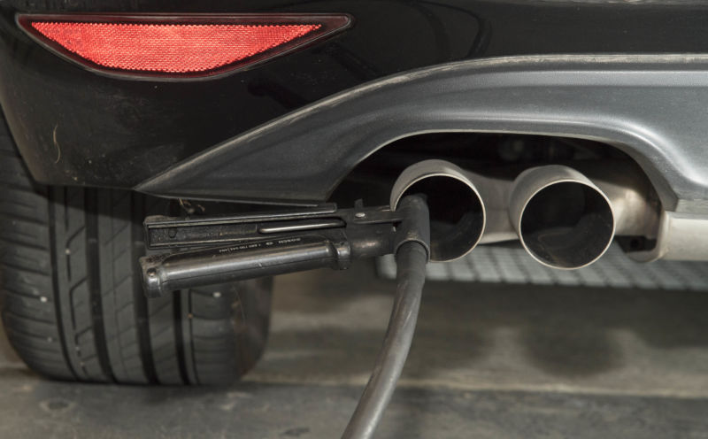 A tube attached to the tailpipe from a sports car performs an emissions test.