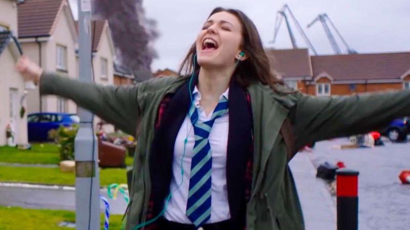 Promotional image of teenage girl singing.