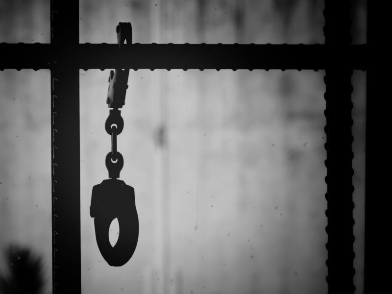Closeup shot of handcuffs hanging from a metal bar in a prison.