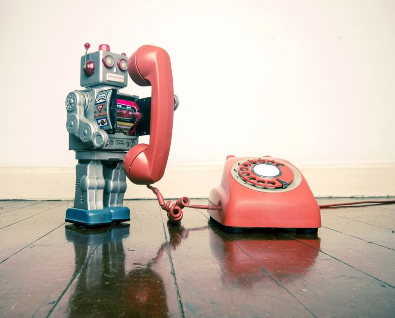 Illustration of a toy robot using a rotary telephone.