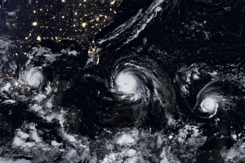 Outer-space view of three hurricanes crossing ocean to the US.