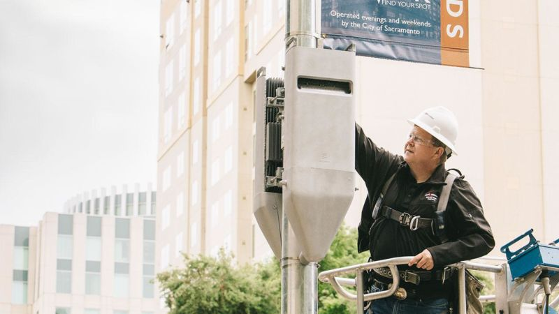 A Verizon construction engineer inspects a pair of radio heads on a mock small cell attached to a pole.