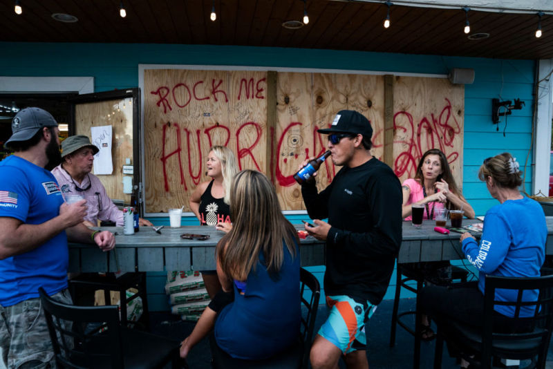Patrons enjoy beverages outside Buster's Beer & Bait, one of the last bars in the area still open, as Hurricane Michael approaches the Florida panhandle, in Panama City Beach on Tuesday, Oct. 09.