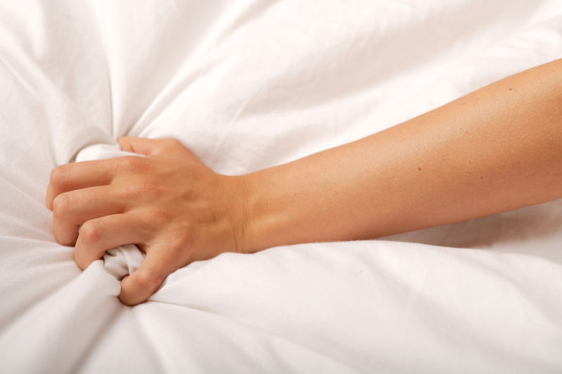 Close up of hand clutching bed sheets