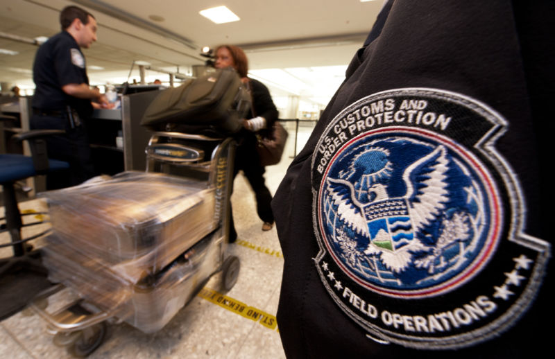 An international air traveler is cleared by a US Customs and Border Protection Officer (L) and is approved to enter the United States inside the US Customs and Immigration area at Dulles International Airport (IAD) , December 21, 2011 in Sterling, Virgina, near Washington, DC.