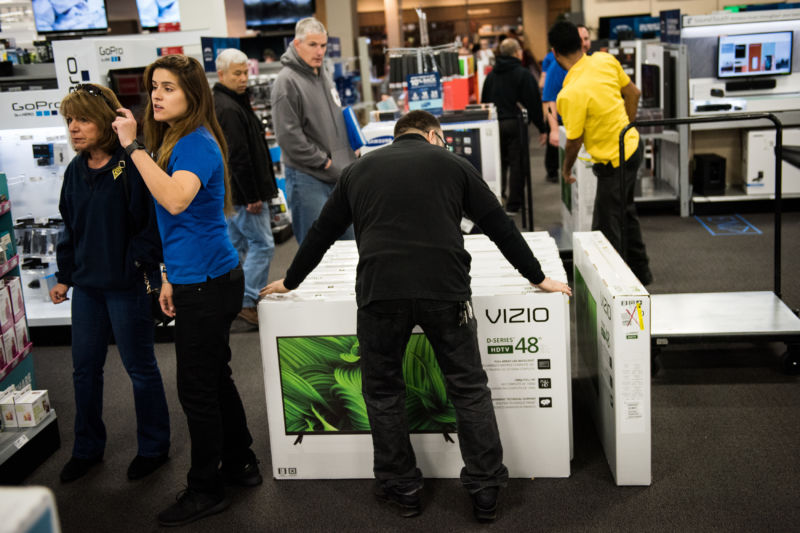 An employee arranges a display of Vizio Inc. high-definition televisions at a Best Buy Inc. store in Paramus, New Jersey, U.S., on Friday, Nov. 25, 2016.