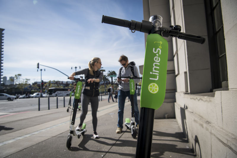 People use a smartphone to unlock a LimeBike shared electric scooter on the Embarcadero in San Francisco, California, on Thursday, May 3, 2018.