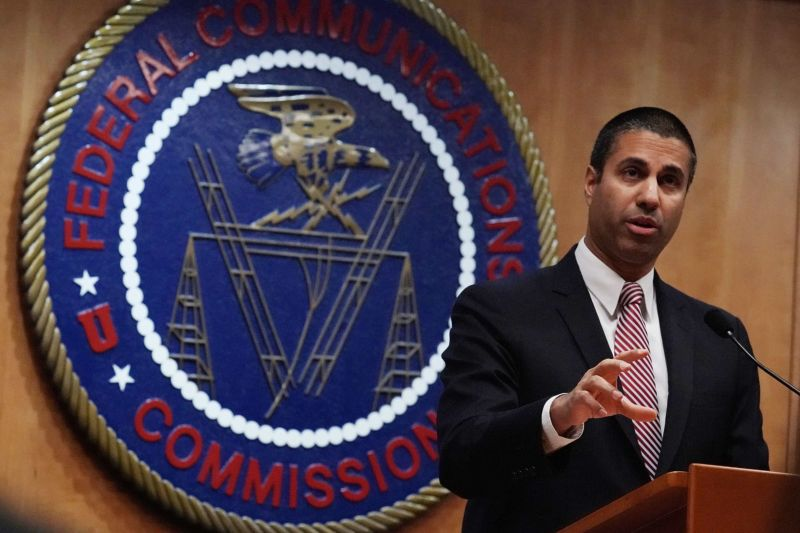 FCC Chairman Ajit Pai talking while standing in front of an FCC seal.
