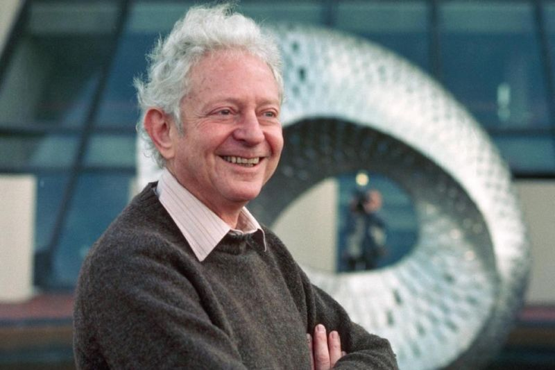 A smiling white-haired man in a sweater.
