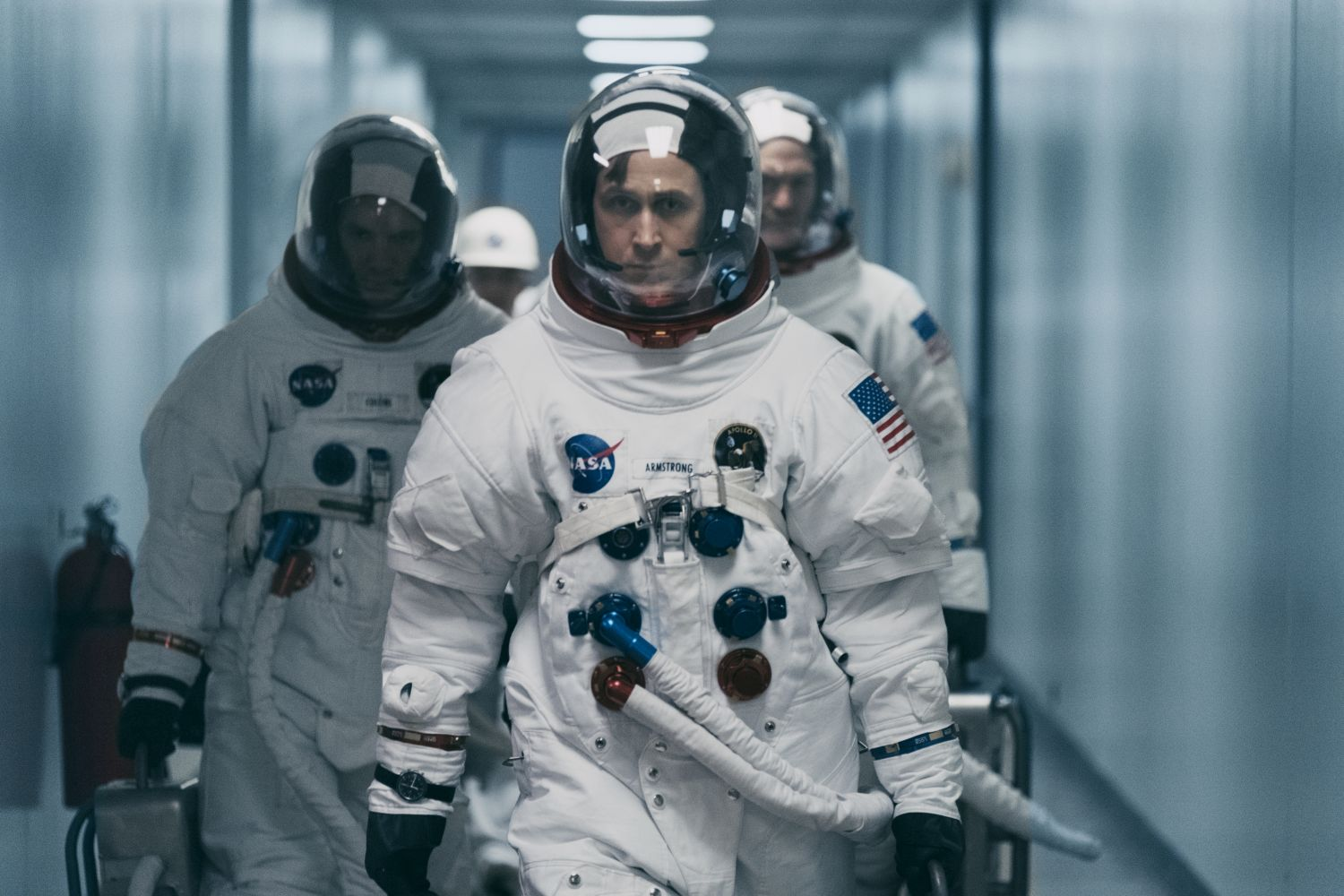 The characters of Armstrong, Mike Collins, and Buzz Aldrin, the crew of Apollo 11, walk out of the suit-up room on their way to their date with destiny.